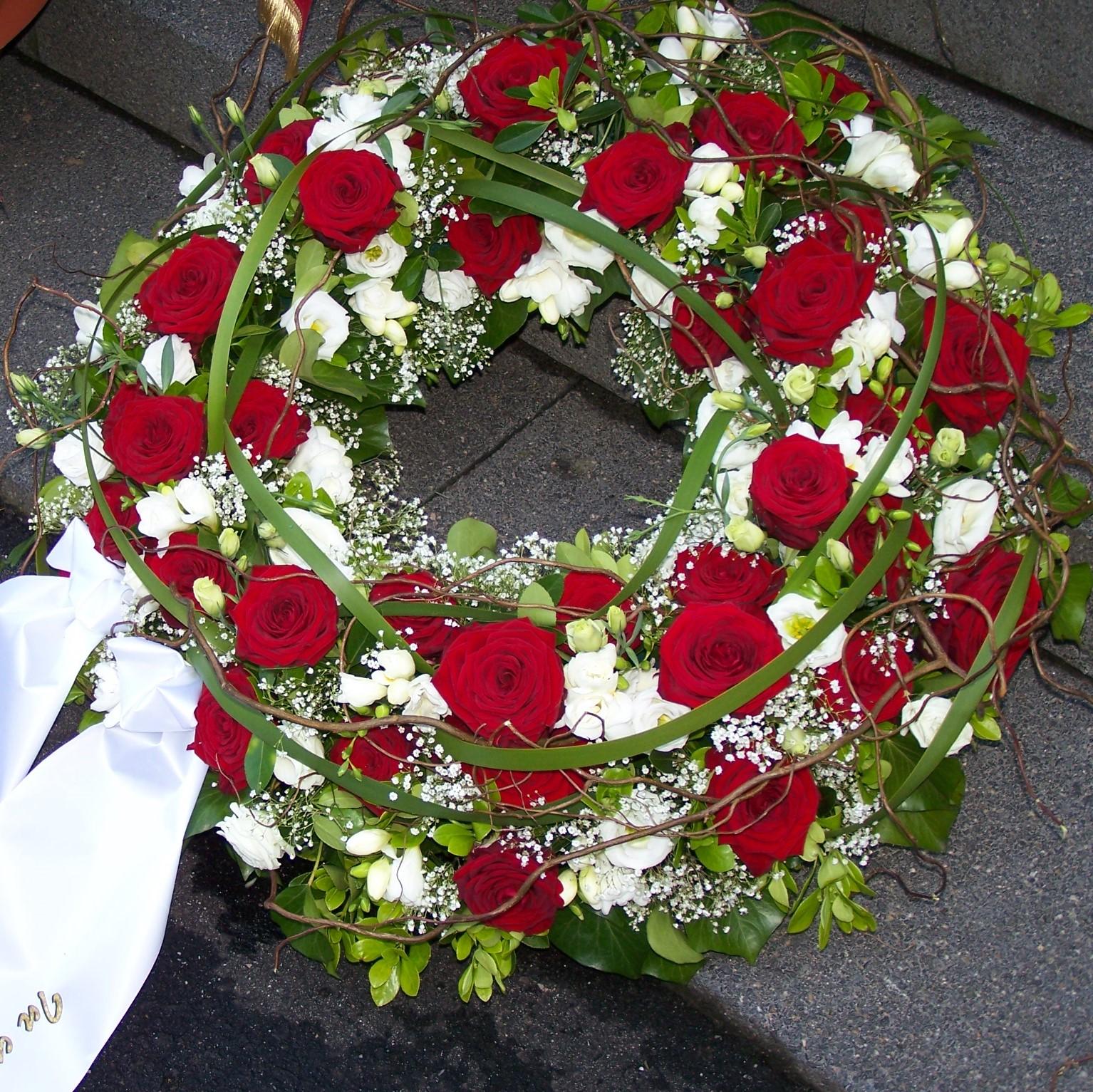 Trauerkranz rundgesteckt mit roten Rosen,weißen Blumen und Grün Bild 1