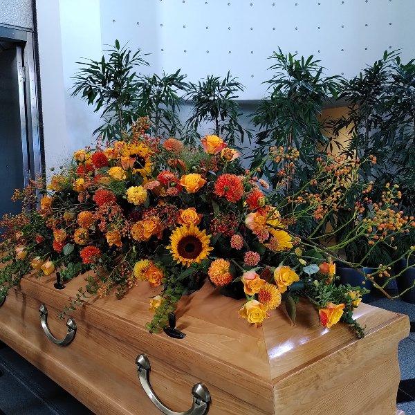 Sargschmuck mit herbstfarben mit Rosen, Sonnenblumen und Hagebutteranken Bild 1