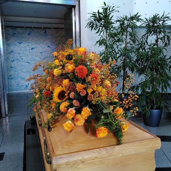 Sargschmuck mit herbstfarben mit Rosen, Sonnenblumen und Hagebutteranken Bild 2