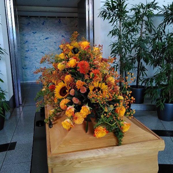 Sargschmuck mit herbstfarben mit Rosen, Sonnenblumen und Hagebutteranken Bild 3