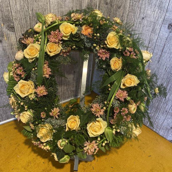 Trauerkranz rundgesteckt mit orangenen Rosen, passenden Blumen und Grün Bild 1