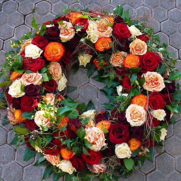 Trauerkranz mit roten und orangenen Rosen Bild 1