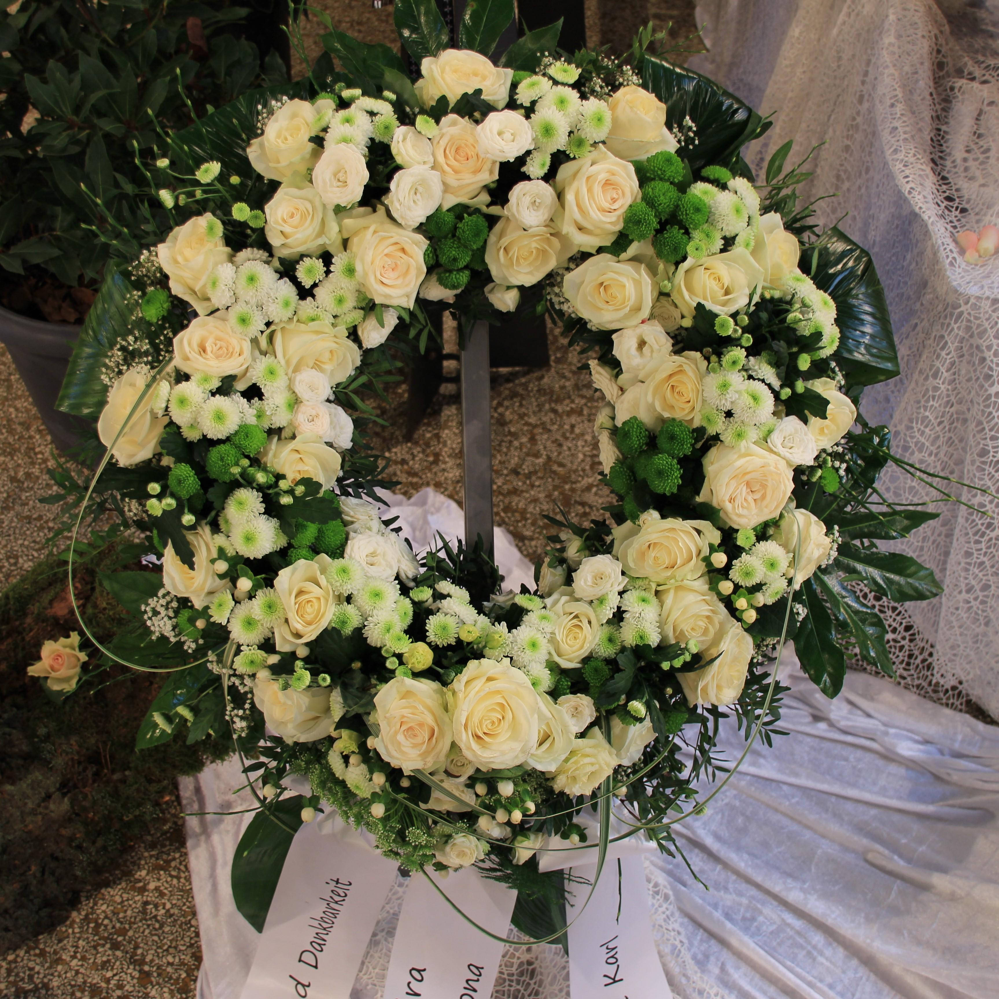 Trauerkranz rundgesteckt mit weißen Rosen, weißen Blumen und Grün Bild 1