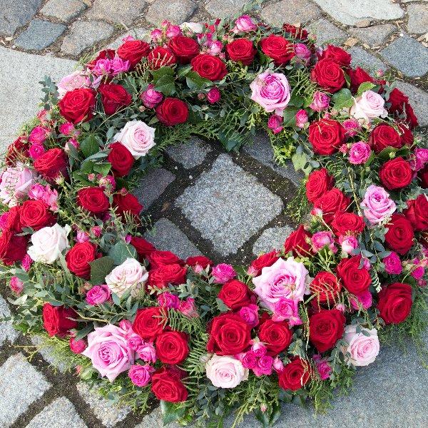 Trauerkranz rundgesteckt in rot/rosa Farbtönen Bild 1
