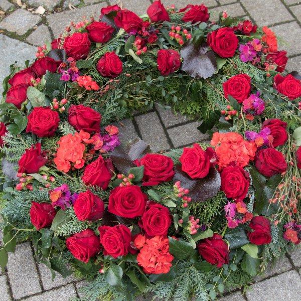 Trauerkranz rundgesteckt mit roten Rosen und Beiwerk Bild 1
