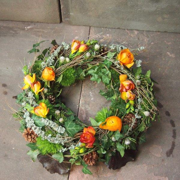 Trauerkranz rundgesteckt, natürlich gesteckt mit viel Grün und Zweigen, Akzent mit Blumen Bild 3