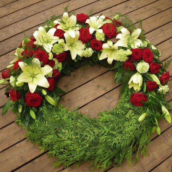 halbrund gesteckter Trauerkranz mit roten Rosen Bild 1