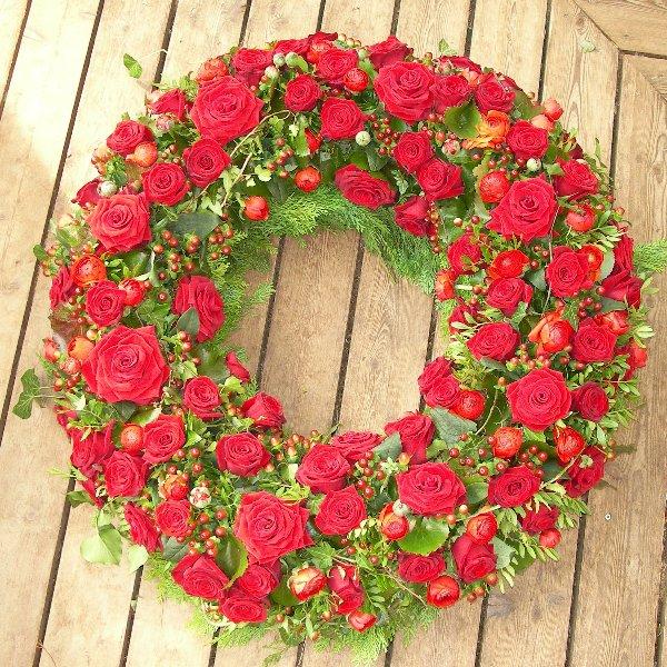 klassischer, rundgesteckter Trauerkranz mit roten Rosen Bild 1